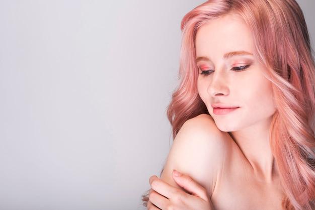 Modello femminile che tiene il suo braccio con copia-spazio