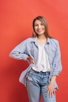 Modello femminile grazioso che posa con un'espressione sorridente del fronte sulla parete rossa