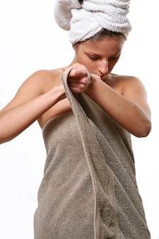 Modello femminile in asciugamano avvolto dopo il bagno