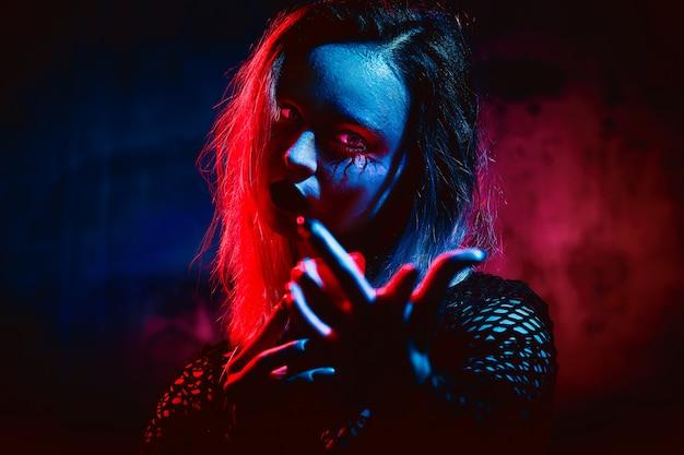 Modello femminile in attrezzatura di halloween che posa con sopra un rosso. splendida ragazza in abiti celebra il giorno dei morti. concetto di halloween, costume da strega, colori vivaci, punk a vapore.