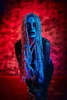 Modello femminile in attrezzatura di halloween che posa con su una parete rossa. splendida ragazza in abiti celebra il giorno dei morti. concetto di halloween, costume da strega, colori vivaci, punk a vapore.