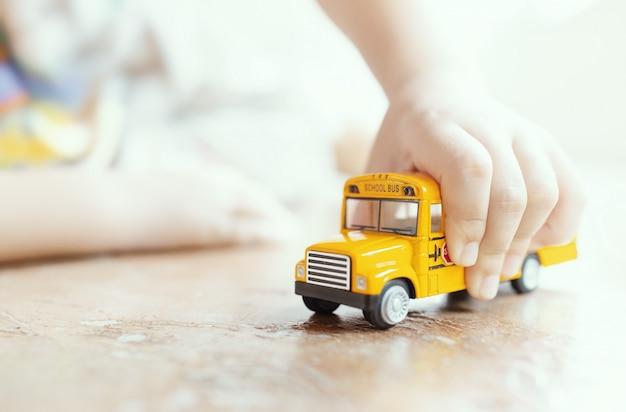 Modello giallo del giocattolo dello scuolabus in mano del bambino composizione bassa in profondità di campo.