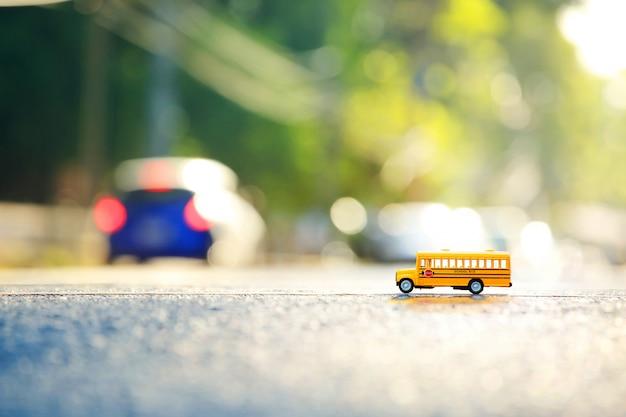 Modello giallo del giocattolo dello scuolabus l'attraversamento della strada composizione nella profondità di campo bassa e scena di pomeriggio.