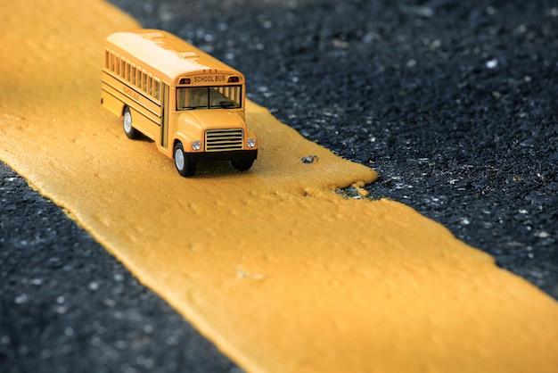 Modello giallo del giocattolo dello scuolabus sulla linea gialla di strada campestre.