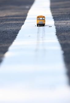 Modello giallo del giocattolo dello scuolabus sulla strada campestre composizione profonda in profondità di campo.