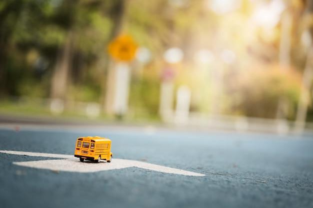 Modello giallo del giocattolo dello scuolabus sulla strada campestre.