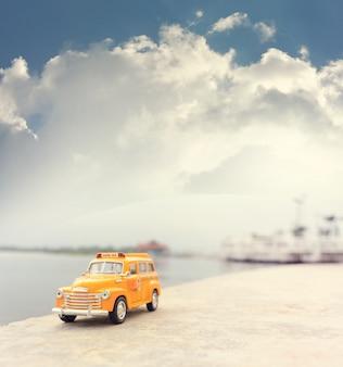 Modello giallo del giocattolo dello scuolabus sulla strada della riva del fiume.