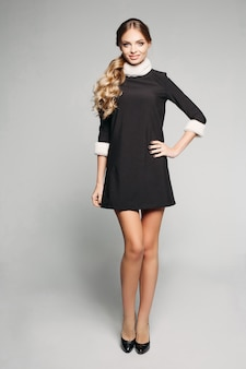 Modello grazioso con capelli biondi ondulati in coda in mini abito nero con rifiniture in pelliccia.