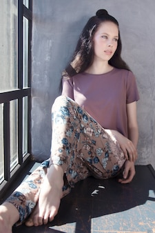 Modello grazioso del brunette che propone sul davanzale di una finestra nel suo vestito di sonno