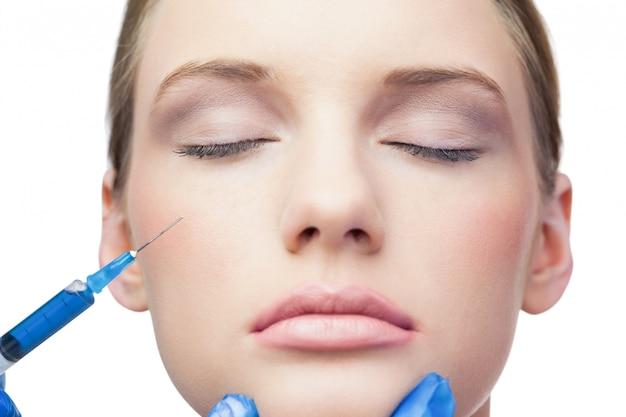 Modello grazioso tranquillo con iniezione di botox sulla guancia