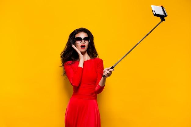 Modello in abito rosso con la bocca aperta prendendo selfie.