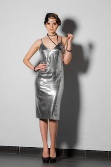 Modello in abito tinsel argento stile retrò con pennacchio in capelli