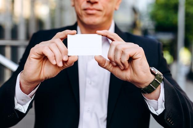 Modello in bianco vuoto bianco del primo piano del biglietto da visita in mani maschii - copi lo spazio