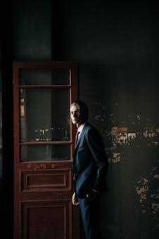 Modello maschile in abito nero e cravatta rossa pone per la pubblicità di abbigliamento maschile. riprese per negozio di abbigliamento maschile