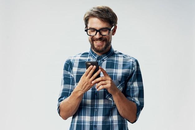 Modello maschio bello con la barba con un telefono che posa nello studio