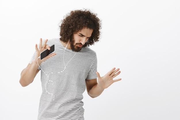 Modello maschio bello spensierato entusiasta con barba e acconciatura afro, ballando e guardando in basso