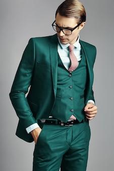 Modello maschio del giovane uomo d'affari bello elegante in un vestito e nei vetri alla moda
