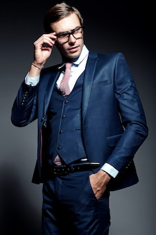 Modello maschio del giovane uomo d'affari bello elegante in vestito blu e vetri alla moda, posanti nello studio