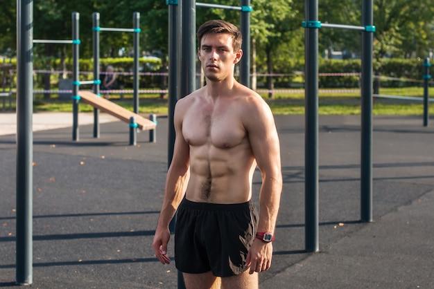 Modello maschio di forma fisica muscolare che posa gli addominali dimostranti senza camicia di sei pacchetti
