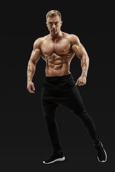 Modello maschio senza camicia che posa il centro muscolare