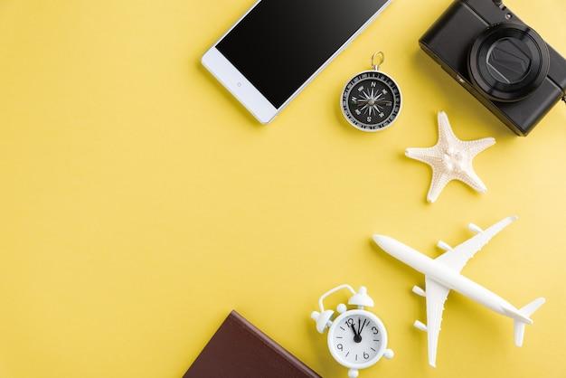 Modello minimo di aereo, aeroplano, stella marina, sveglia, bussola e schermo vuoto dello smartphone