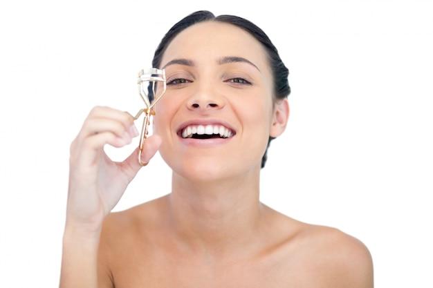 Modello naturale sorridente con il bigodino del ciglio che esamina macchina fotografica