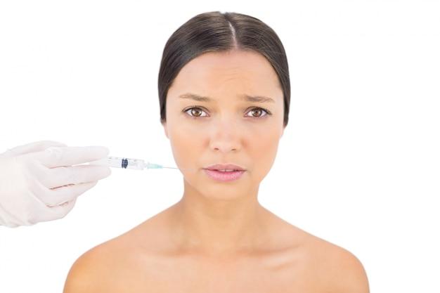 Modello nudo ansioso con iniezione di botox intorno alla bocca
