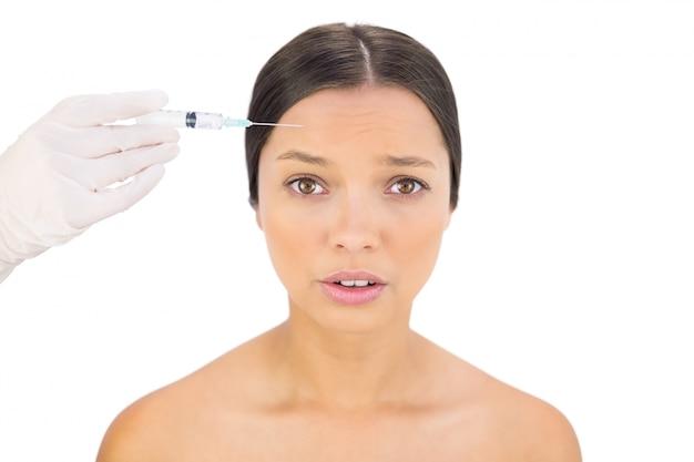 Modello nudo ansioso con iniezione di botox sulla fronte