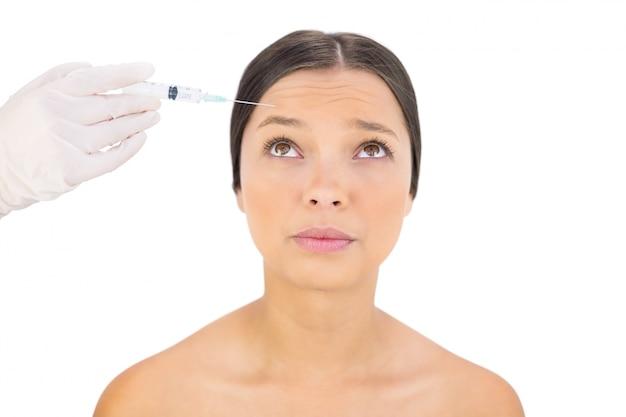 Modello nudo preoccupato con iniezione di botox sulla fronte
