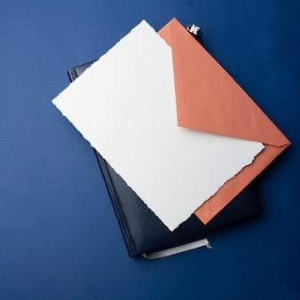 Modello per inviti, saluti. su uno sfondo blu, un foglio di carta bianco, una busta, un quaderno, un anello con pietre e candele decorative. design minimalista per matrimonio, compleanno.