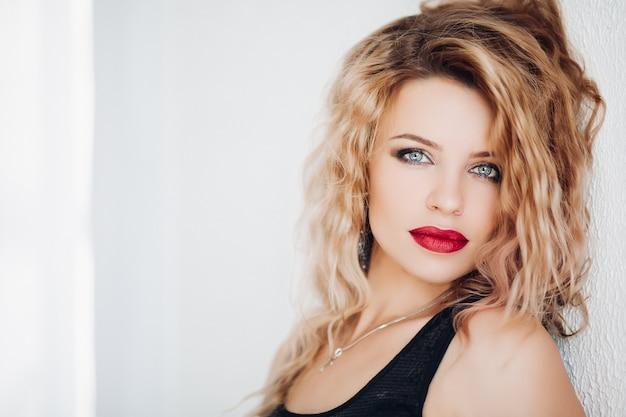 Modello sensuale con capelli biondi ondulati e le labbra rosse che esaminano macchina fotografica contro il bianco.