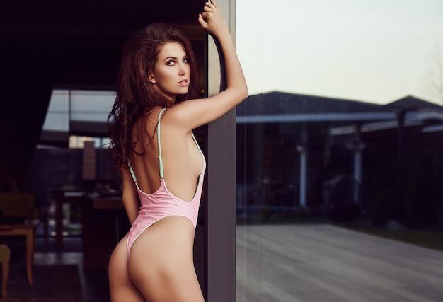 Modello sensuale del brunette in costume da bagno di modo che propone sul terrazzo