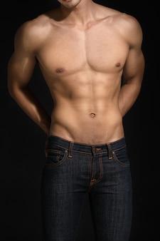 Modello senza camicia uomo sexy con jean in piedi su sfondo nero