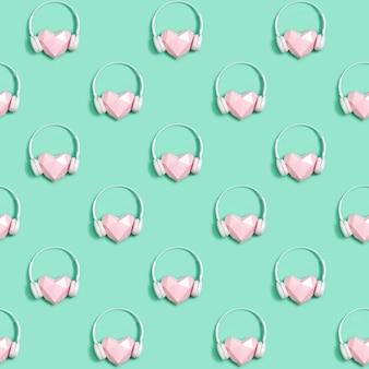 Modello senza cuciture con cuore rosa di carta in cuffie bianche, concetto per festival musicali, stazioni radio, amanti della musica