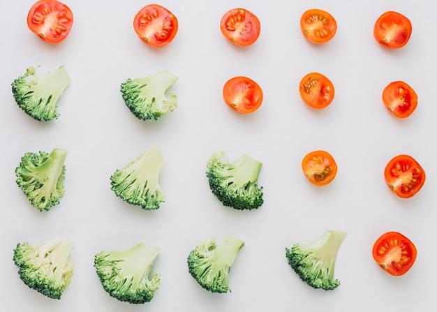 Modello senza cuciture dei broccoli e dei pomodori ciliegia divisi in due isolati su fondo bianco