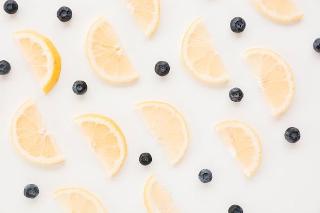 Modello senza cuciture di mirtilli e fette di limone su sfondo bianco