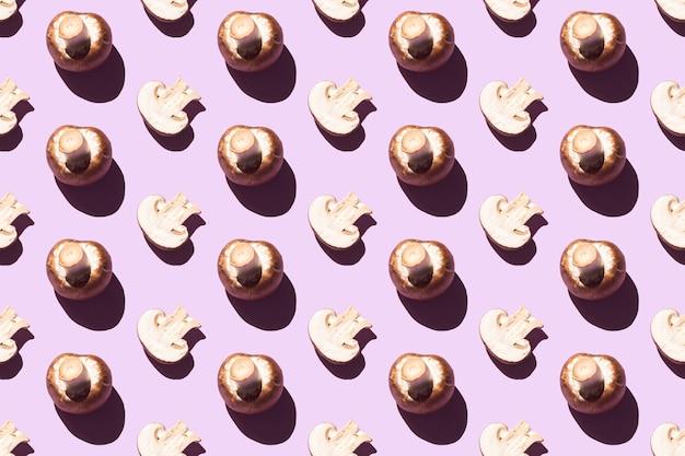 Modello senza giunture di champignon tagliati e interi su uno sfondo viola