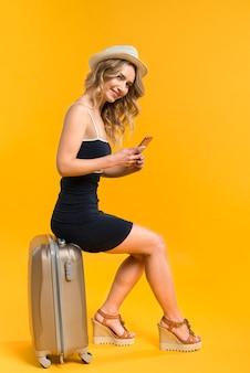 Modello sorridente che si siede sulla valigia e che tiene telefono cellulare