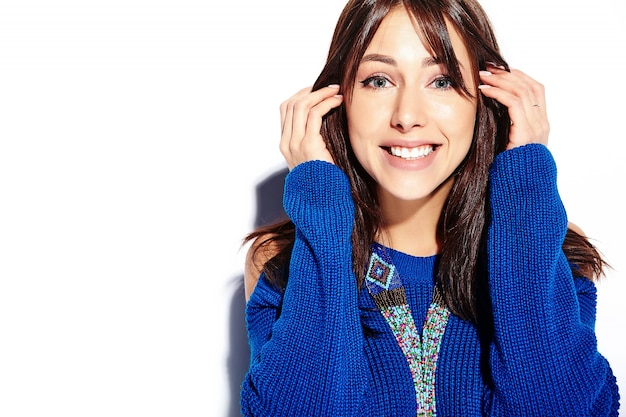 Modello sorridente della donna castana dei bei pantaloni a vita bassa in maglione blu di estate alla moda casuale isolato su fondo bianco