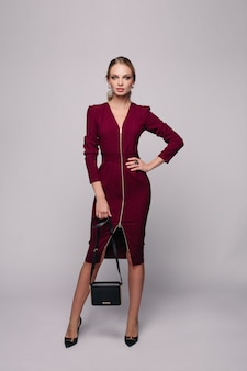 Modello sottile ed elegante in abito con una borsetta.