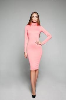 Modello splendido ed elegante in abito e tacchi rosa casual che abbracciano il corpo.