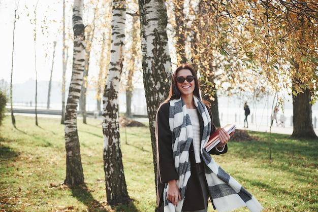 Modello splendido. il giovane castana sorridente in occhiali da sole sta nel parco vicino agli alberi e tiene il blocco note
