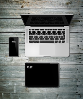 Modello stabilito del computer portatile, della compressa e del telefono su una tavola di legno