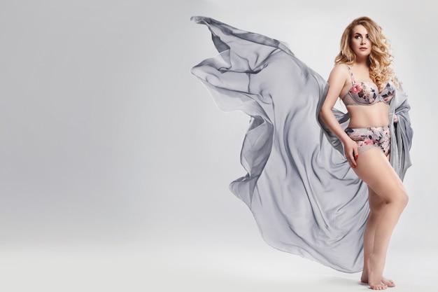 Modello taglie forti che indossa lingerie e pezzo di tessuto sventolante