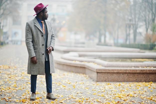 Modello uomo elegante in cappotto grigio, cravatta giacca e cappello rosso posato in strada tempo nebbioso
