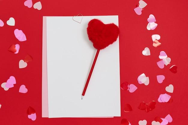 Modello vuoto per lettere romantiche su spazio rosso. penna rossa a forma di cuore in pelliccia