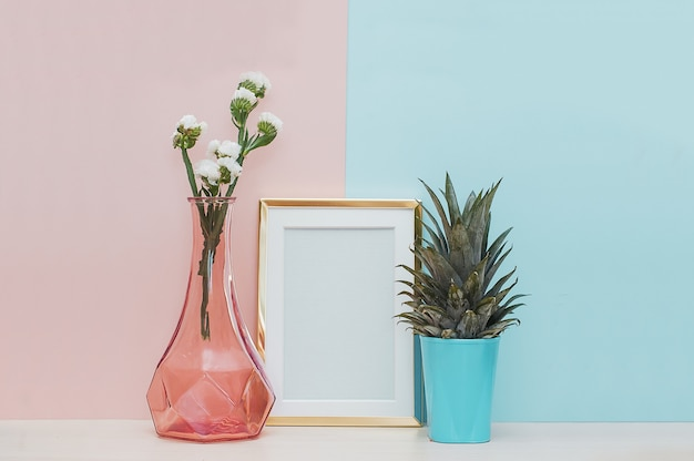 Modern home decor mock up con cornice dorata, vaso e pianta tropicale sul retro blu rosa
