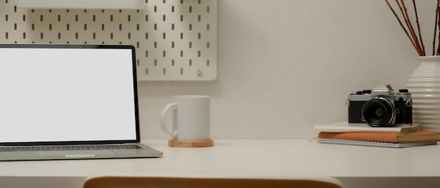 Moderna area di lavoro con laptop, tazza di caffè, macchina fotografica, agenda, decorazioni
