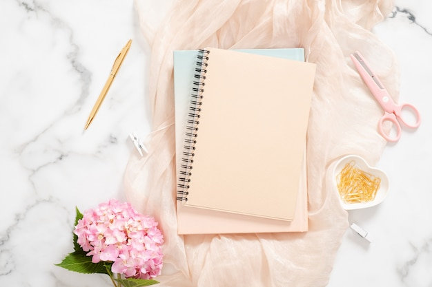 Moderna area di lavoro per ufficio a casa con fiori di ortensia rosa, coperta pastello, blocco note di carta bianca, articoli di cancelleria dorati e accessori femminili