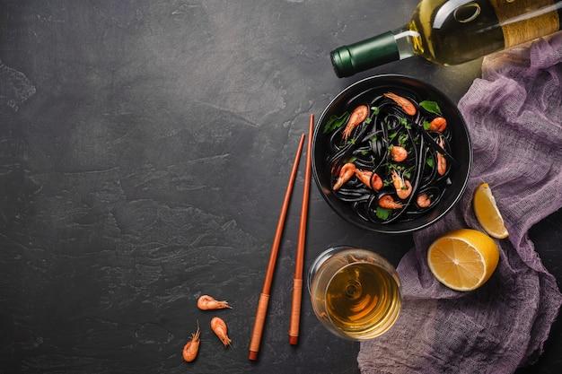Moderna cena giapponese, cibo mediterraneo, inchiostro nero di seppia, pasta spaghetti con frutti di mare, olio d'oliva e basilico, sul tavolo arrugginito scuro.